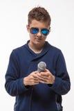 Morenita emocional del muchacho del adolescente en gafas de sol con un micrófono Fotos de archivo libres de regalías
