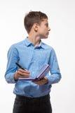 Morenita emocional del muchacho del adolescente en una camisa azul con un diario y una pluma a disposición Fotografía de archivo