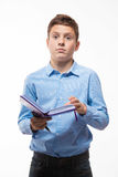 Morenita emocional del muchacho del adolescente en una camisa azul con un diario y una pluma a disposición Foto de archivo libre de regalías