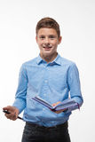 Morenita emocional del muchacho del adolescente en una camisa azul con un diario y una pluma a disposición Imagen de archivo