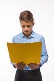 Morenita emocional del muchacho en una camisa azul con la hoja de papel amarilla para las notas Fotografía de archivo libre de regalías