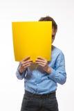 Morenita emocional del muchacho en una camisa azul con la hoja de papel amarilla para las notas Foto de archivo libre de regalías
