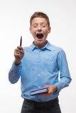 Morenita emocional del muchacho en una camisa azul con un diario y una pluma a disposición fotografía de archivo