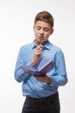 Morenita emocional del muchacho en una camisa azul con un diario y una pluma a disposición fotos de archivo