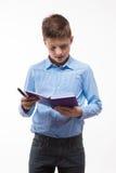 Morenita emocional del muchacho en una camisa azul con un diario y una pluma a disposición foto de archivo