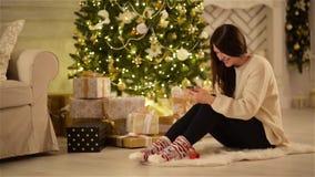 Morenita emocional hermosa que manda un SMS en su artilugio y que sonríe al lado del árbol de navidad grande y cajas con los rega almacen de video