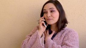 morenita en la capa rosada que habla en concepto del teléfono, de la forma de vida, de la comunicación y de la tecnología almacen de metraje de vídeo