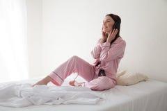 Morenita en los pijamas rosados que escuchan la música con los auriculares en la cama Imágenes de archivo libres de regalías