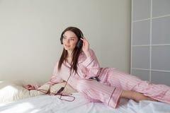 Morenita en los pijamas rosados que escuchan la música con los auriculares en la cama Imagenes de archivo