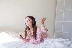 Morenita en los pijamas rosados que escuchan la música con los auriculares en la cama Foto de archivo libre de regalías