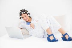 Morenita en rodillos del pelo y zapatos de la cuña usando su ordenador portátil para sh Imagenes de archivo