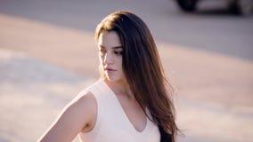 Morenita encantadora joven en la presentación blanca en la calle que mira abajo almacen de video
