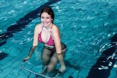 Morenita feliz apta usando la bicicleta estática subacuática Foto de archivo libre de regalías