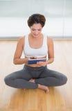 Morenita feliz deportiva que se sienta en actitud del loto y que usa la tableta Foto de archivo