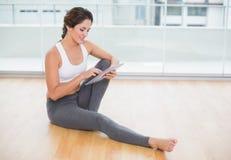 Morenita feliz deportiva usando la tableta que se sienta en el piso Imagenes de archivo