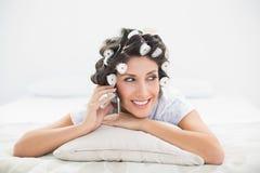 Morenita feliz en los rodillos del pelo que mienten en su cama que hace un teléfono c Fotos de archivo libres de regalías