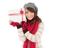 Morenita festiva que sostiene el regalo blanco y rojo Imagenes de archivo