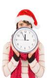 Morenita festiva que sostiene un reloj Foto de archivo