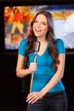 Morenita hermosa con el micrófono que se coloca en barra Imagen de archivo libre de regalías