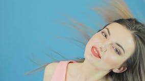 Morenita hermosa con el pelo largo, el vestido del rosa y la sonrisa encantadora presentando en fondo azul en estudio almacen de metraje de vídeo