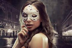 Morenita hermosa con la máscara veneciana Mujer joven y hermosa en el fondo veneciano de la visión imagen de archivo