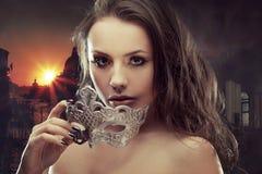 Morenita hermosa con la máscara veneciana Mujer joven y hermosa en el fondo veneciano de la visión fotografía de archivo