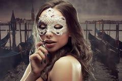 Morenita hermosa con la máscara veneciana Mujer joven y hermosa en el fondo veneciano de la visión, góndolas fotos de archivo