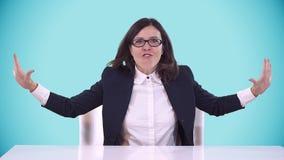 Morenita hermosa con los vidrios que se sientan en un traje de negocios en el escritorio y los gritos de oficina Fondo para una t almacen de metraje de vídeo