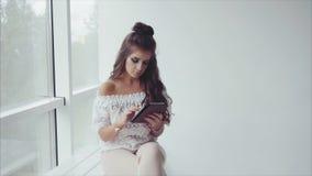Morenita hermosa de la mujer usando su tableta en el fondo blanco cerca de la ventana almacen de metraje de vídeo