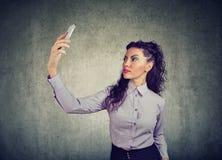Morenita hermosa en equipo formal usando selfie del smartphone y el tomar en fondo gris fotos de archivo libres de regalías