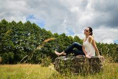 Morenita hermosa en un canto rodado grande Foto de archivo libre de regalías