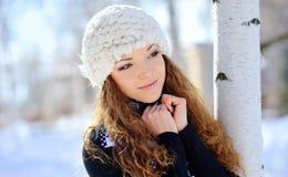 Morenita hermosa en un sombrero blanco que coloca el abedul cercano en invierno Foto de archivo libre de regalías