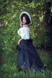 Morenita hermosa en un sombrero blanco y negro grande imagenes de archivo