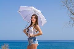 Morenita hermosa joven con el paraguas blanco Imagen de archivo libre de regalías
