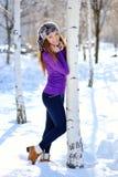 Morenita hermosa que coloca el abedul cercano en invierno Imagen de archivo