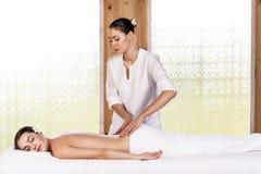 Morenita hermosa que disfruta de un masaje fotografía de archivo libre de regalías