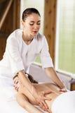 Morenita hermosa que disfruta de un masaje fotografía de archivo