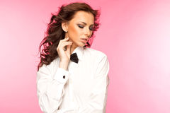Morenita hermosa que lleva un arco del lazo negro y una camisa blanca Imagenes de archivo