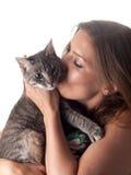 Morenita hermosa sonriente que besa y que acaricia su gato gris lindo Imagen de archivo