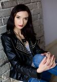 Morenita joven atractiva en la chaqueta de cuero Imagenes de archivo