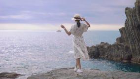 Morenita joven atractiva en la situación del vestido del verano del sombrero y de la luz al borde de un acantilado y la mirada de almacen de video