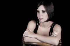 Morenita joven atractiva en una silla Foto de archivo libre de regalías