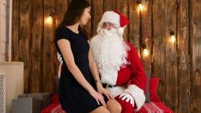 Morenita joven atractiva que se sienta en el revestimiento de Santa Claus y que dice sus deseos de Chistmas almacen de metraje de vídeo