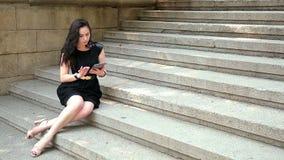 Morenita joven atractiva que se sienta en las escaleras y mandar un SMS almacen de metraje de vídeo