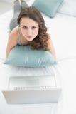 Morenita joven casual con el ordenador portátil que miente en cama Fotografía de archivo