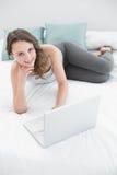 Morenita joven casual sonriente con el ordenador portátil en cama Imagenes de archivo