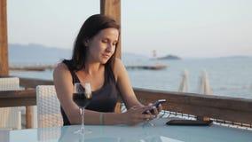 Morenita joven con el vidrio de vino rojo usando su Smartphone mientras que se sienta en café por el mar en la puesta del sol Imágenes de archivo libres de regalías