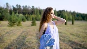 Morenita joven con la ropa informal que lleva del maquillaje y mirada abajo en el fondo del campo con los árboles metrajes