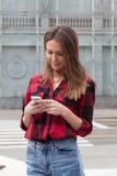 Morenita joven con un teléfono elegante Foto de archivo