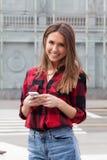 Morenita joven con un teléfono elegante Fotografía de archivo libre de regalías